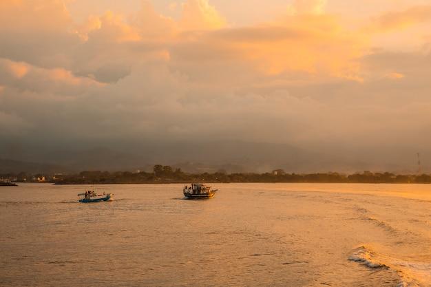 Roatan, honduras: vissersboten in de zee bij zonsondergang gezien vanaf de veerboot richting roatan island