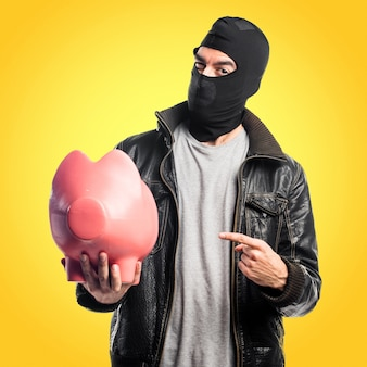 Robber die een piggybank op kleurrijke achtergrond houdt