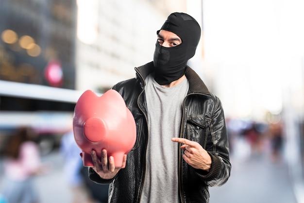 Robber die een piggybank op ongerichte achtergrond houdt