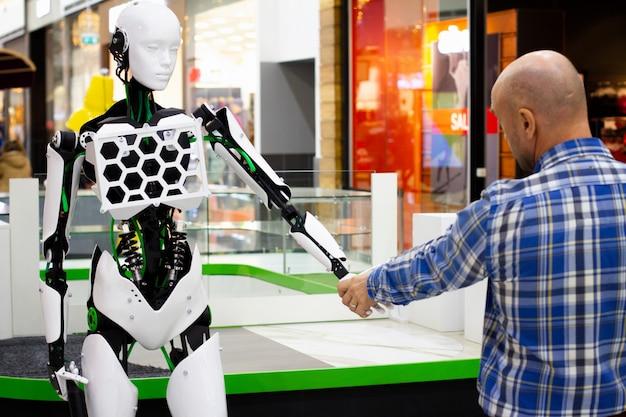 Robot en menselijke handdruk, introductie van nieuwe technologieën in het menselijk leven. een man begroet een robot