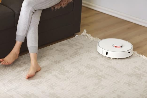 Robotachtige stofzuiger die de ruimte schoonmaakt terwijl vrouw die op bank rust. selectieve focus op robotic