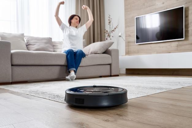Robotachtige stofzuiger die de ruimte schoonmaken terwijl vrouw die op bank rust
