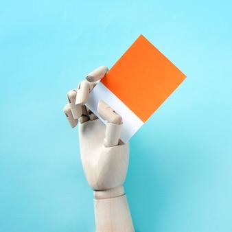 Robothand die een blanco papier vasthoudt