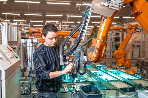 Robotisering van de moderne industrie in de fabriek. introductie van nieuwe robotarmen ter vervanging van menselijke hulpbronnen