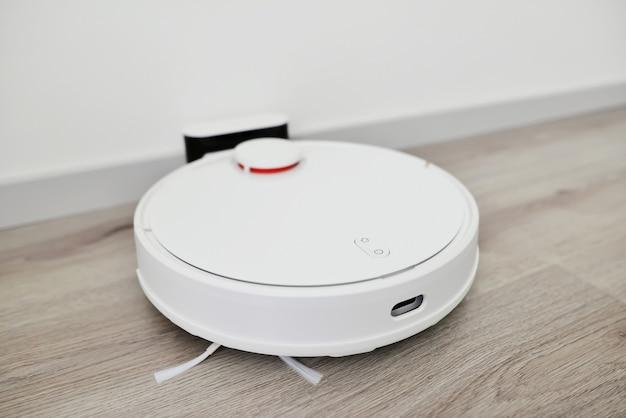 Robotstofzuiger keert terug naar de lading na het schoonmaken van de kamer modern slim huishouden. de witte (robot) stofzuiger wordt opgeladen op zijn basis.