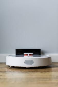 Robotstofzuiger op houten vloer. zijaanzicht. slim huisconcept. automatische reiniging.