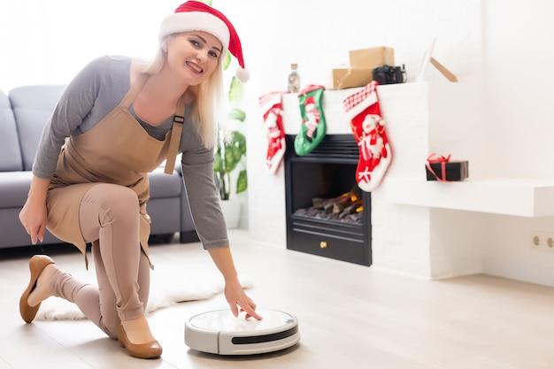 Robotstofzuiger op laminaat houten vloer slimme reinigingstechnologie. kerstboom