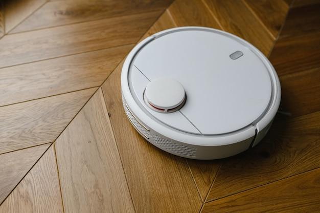 Robotstofzuiger op laminaatvloer slimme reinigingstechnologie.
