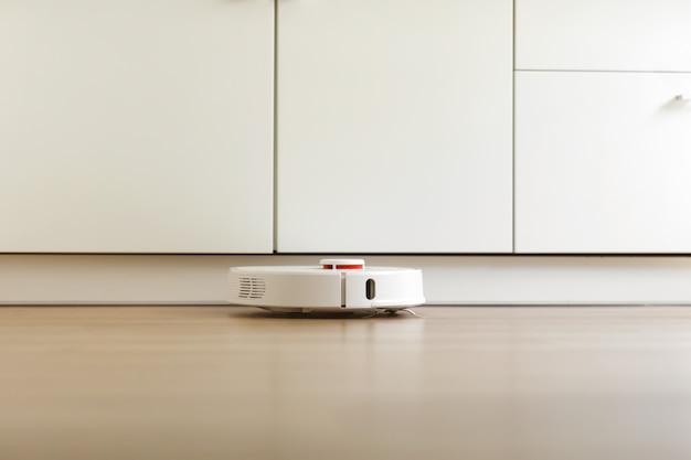 Robotstofzuiger voert op een bepaald moment automatische reiniging van het appartement uit. witte robotstofzuiger. huis schoonmaken. slimme woning. selectieve aandacht