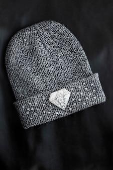 Rocailles geborduurde broche in een vorm van diamant op gebreide muts op zwart oppervlak
