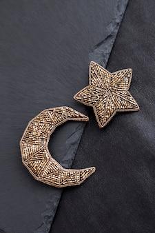 Rocailles geborduurde broches in de vorm van maan en ster op zwarte achtergrond. plat leggen