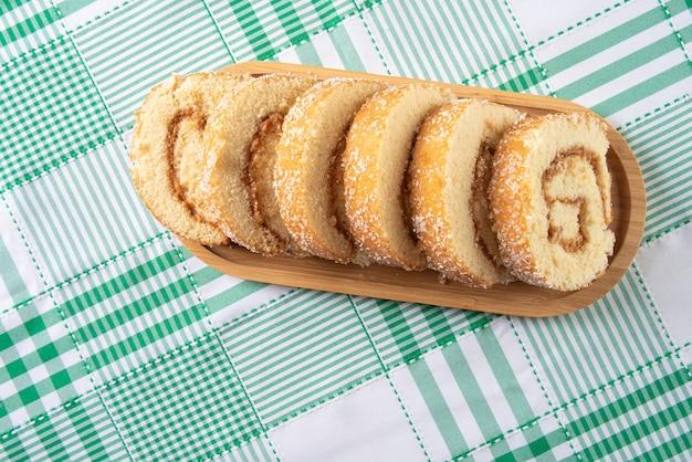 Rocambole, gesneden rocambole gevuld met dulce de leche op een houten dienblad op een tafel met geruit tafelkleed. donkere achtergrond, bovenaanzicht.