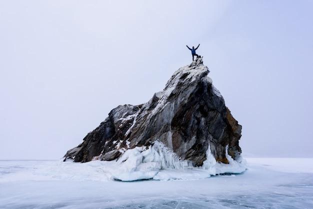 Rock klimmer op de top van berg eiland. sport en actief leven
