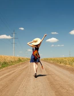 Rock meisje met gitaar op platteland.