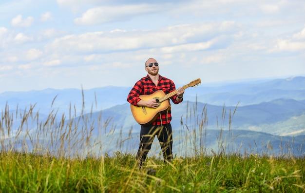 Rock met je sexy man met gitaar in geruit hemd hipster mode western kamperen en wandelen