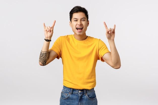 Rock-n-roll baby. opgewonden en speelse knappe aziatische getatoeëerde hipster-man in geel t-shirt, met heavy metal-gebaren en schreeuwend opgewonden, staande witte muur vrolijk