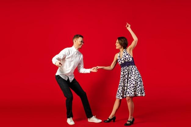 Rock n roll. ouderwetse ouderwetse jonge vrouw dansen geïsoleerd op rode studio achtergrond. jonge stijlvolle man en vrouw.
