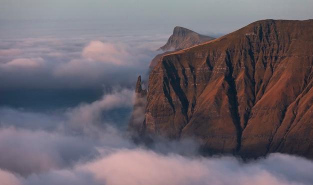 Rock witch's finger bij dageraad. wolken bedekten de atlantische oceaan. faeröer, europa.