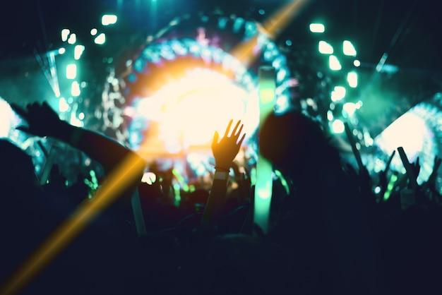 Rockconcert met silhouetten mensen in gelukkig gebaar en het verhogen van de handen voor cheer up