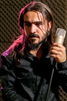 Rocker holding microfoon en wegkijken