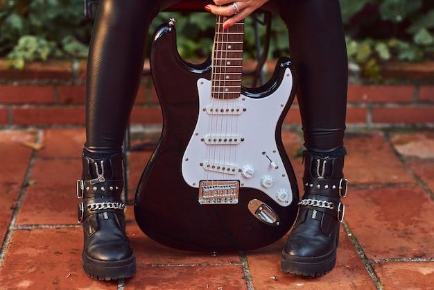 Rocker vrouw poseren met een gitaar.