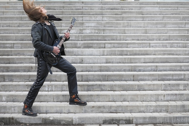 Rockgitarist op de trap. een muzikant met een basgitaar in een leren pak. metalist met een gitaar op de achtergrond van industriële stap.