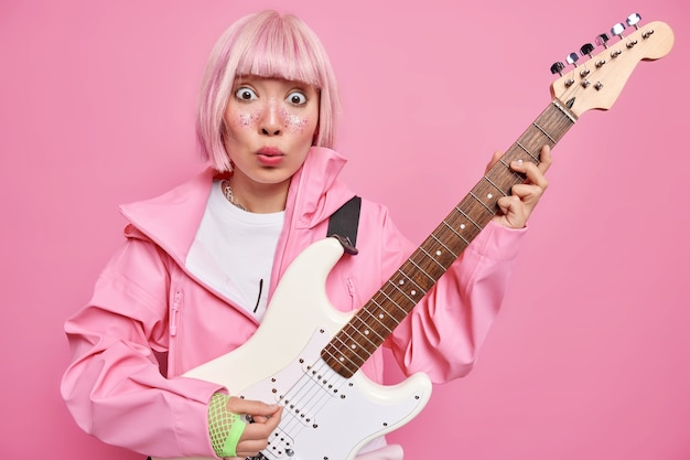 Rockmuziek concept. verrast beroemde gitarist speelt op basgitaar die populair is rocker geschokt om te presteren op stange voor publiek draagt modieuze kleding