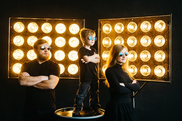 Rockster familie. stijlvolle familie in zwarte kleding en bril in het licht van de stralen. rock-n-roll-muziek.