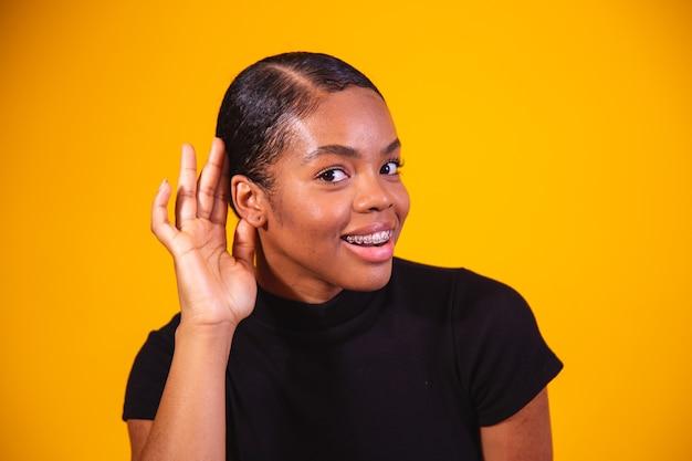 Roddels concept. nieuwsgierige jonge afro-vrouw die hand in de buurt van oor houdt, probeert interessante informatie te horen, vrolijke koreaanse vrouw die afluistert op gele studioachtergrond, panorama met kopieerruimte.