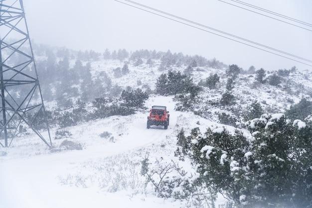 Rode 4x4 off-road auto op een besneeuwde weg tijdens zware sneeuwval.