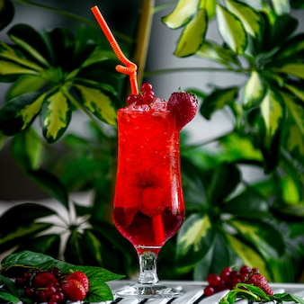 Rode aardbeicocktail versierd met aardbei en cranberry