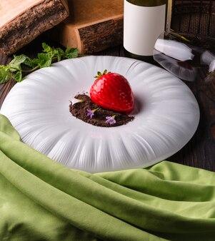 Rode aardbeidessertcake met chocoladeschilfers en viooltjes op een grote witte plaat.