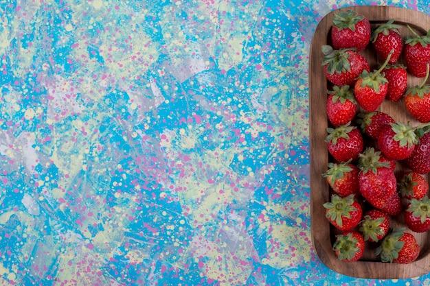 Rode aardbeien in een houten schotel op blauwe achtergrond