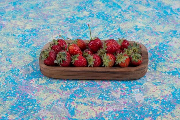 Rode aardbeien in een houten schotel op de blauwe tafel