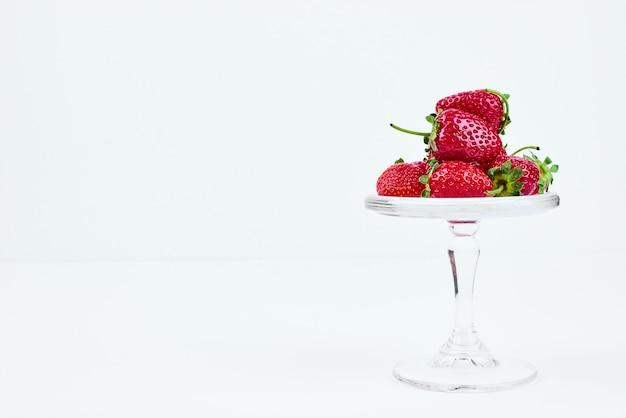 Rode aardbeien op een glazen standaard.