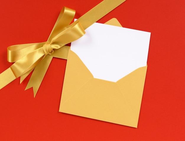 Rode achtergrond gouden kerst cadeau lint boog met lege uitnodiging of groeten kaart diagonaal