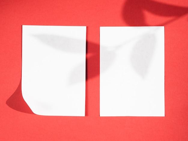 Rode achtergrond met een bladtakschaduw op twee witte dekens