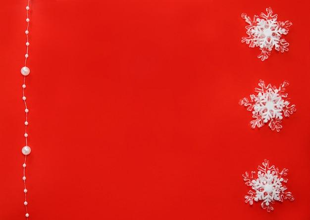 Rode achtergrond met witte feestelijke sneeuwvlokken en parels aan een draad.