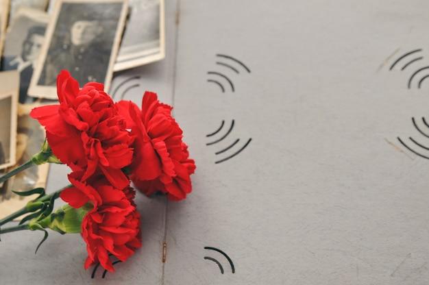 Rode anjers op de achtergrond van een oud fotoalbum met militaire foto's. dag van herdenking en militaire glorie.