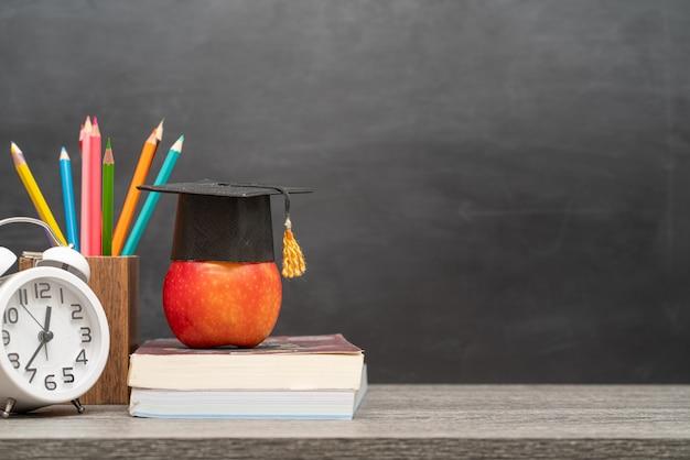 Rode appel, boeken en potlodenhouder op het bureau
