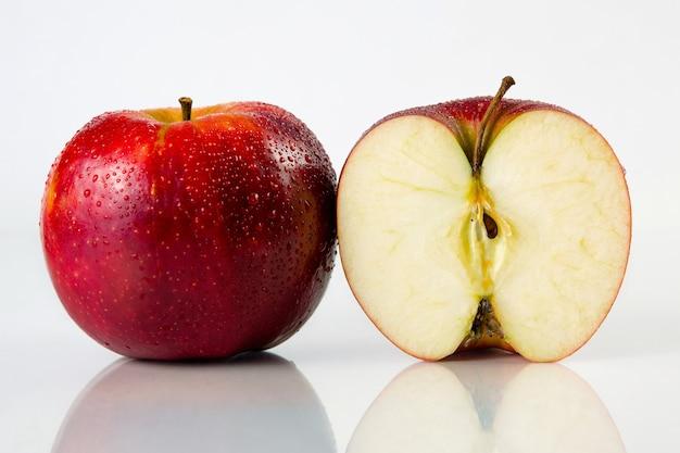 Rode appel en een half met druppels water op een witte achtergrond met reflectie