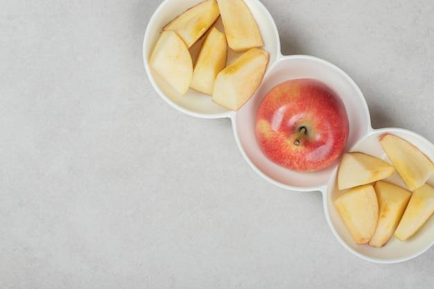 Rode appel en plakjes in witte kommen