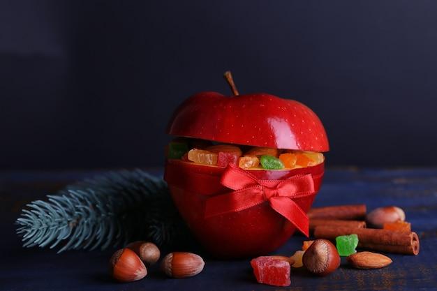 Rode appel gevuld met gedroogde vruchten met kaneel, takje dennenboom en hazelnoot op een houten tafel in kleur en donkere achtergrond