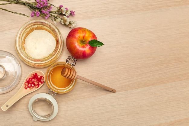 Rode appel, granaatappel en honingpot voor joods nieuwjaar op houten bord