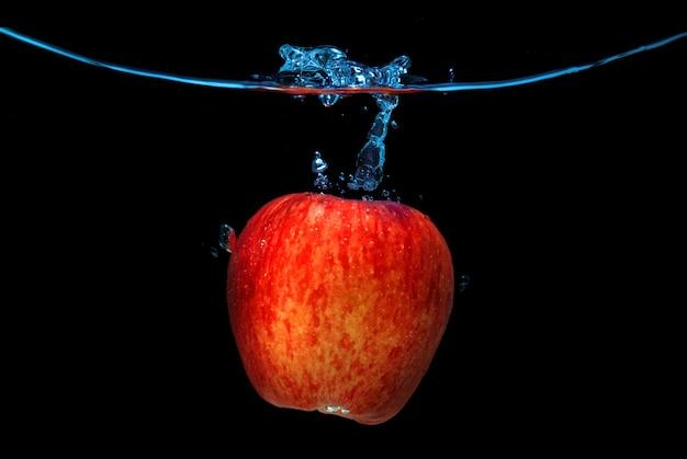 Rode appel in het water gevallen met splash geïsoleerd op zwart