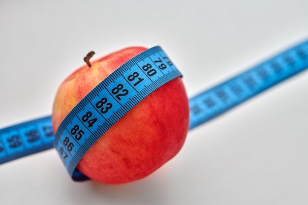 Rode appel met blauw meetlint eromheen geïsoleerd op wit
