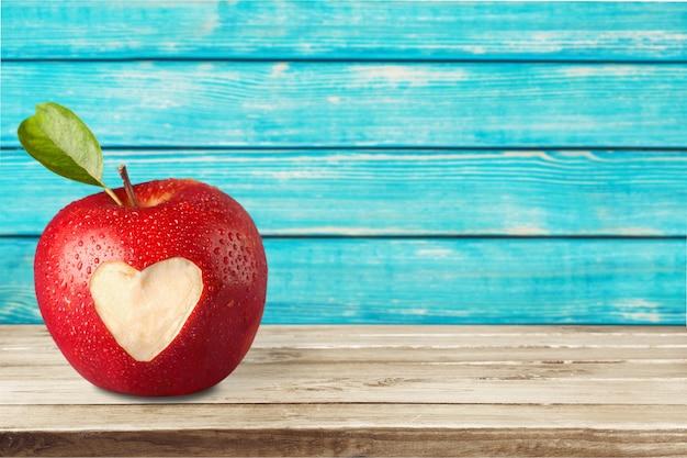 Rode appel met een hartvormige uitsnede. op achtergrond