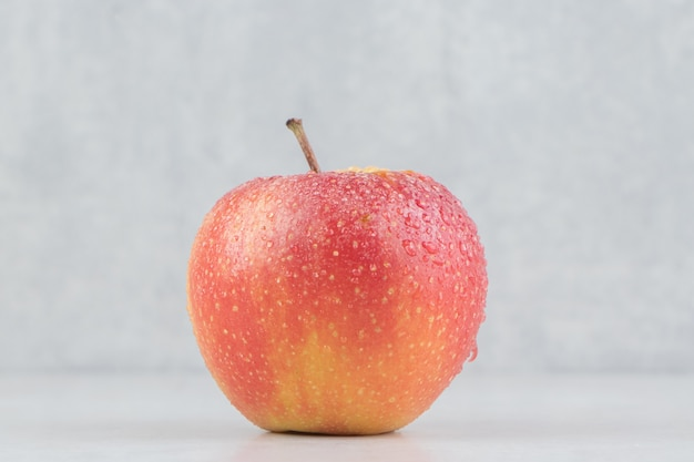 Rode appel met waterdruppels op stenen tafel.