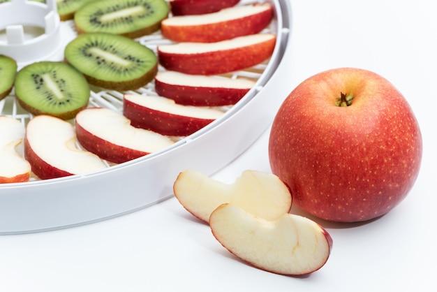 Rode appel op de achtergrond van een dehydrator-bak met appelsplakken.