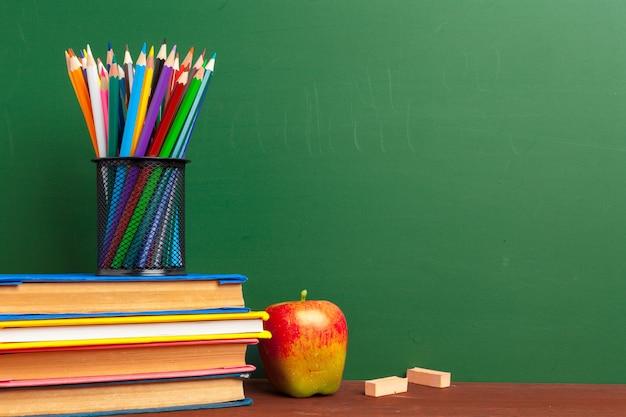Rode appel op een stapel boeken, papier en potlood op het bureau
